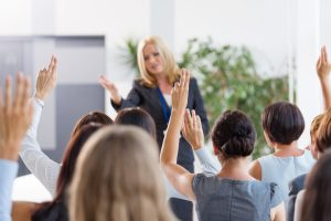 Group of businesswomen attending a seminar, raising their hands.